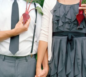 couple holding hands and holding beets in front of their hearts