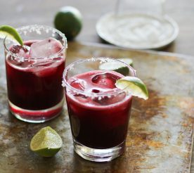 beet margarita on table garnished with lime