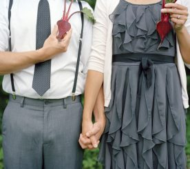 young couple with halves of beetroots in place of heart